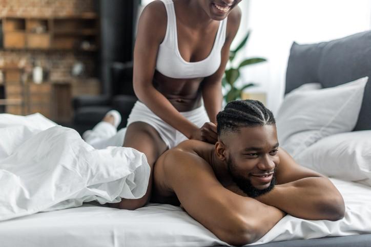 vrouw masseert man in bed