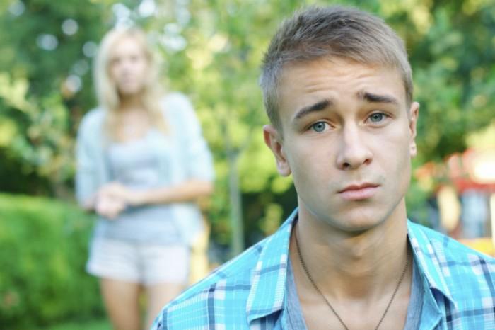 jongen denkt na terwijl zijn vriendin achter hem staat