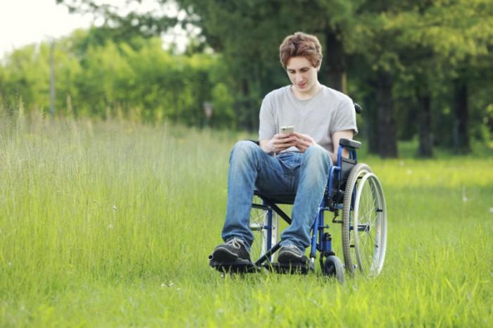 jongen met fysieke beperking en gsm