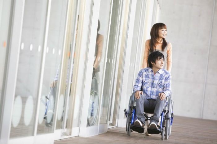 Aziatisch meisje duwt jongen in een rolstoel