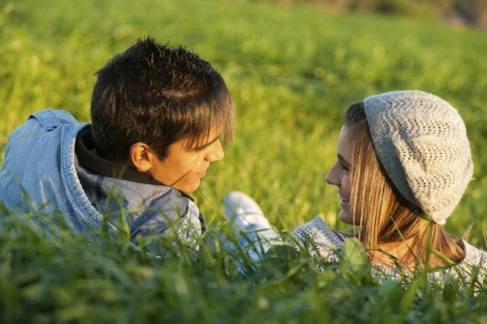 koppel praat met elkaar liggend in het gras