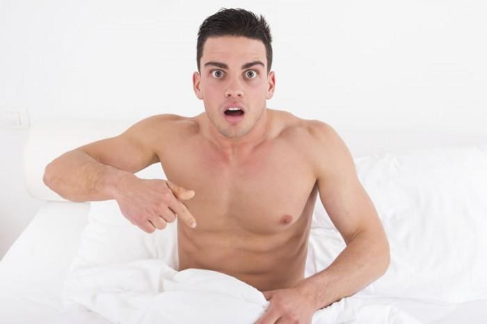 Man met verbaasde blik in bed